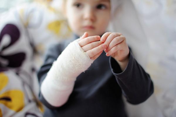Little girl showing her bandaged hand